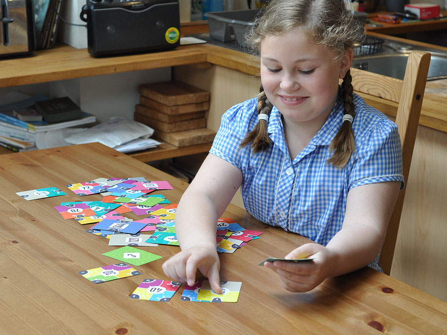 Child at home with times tables cards